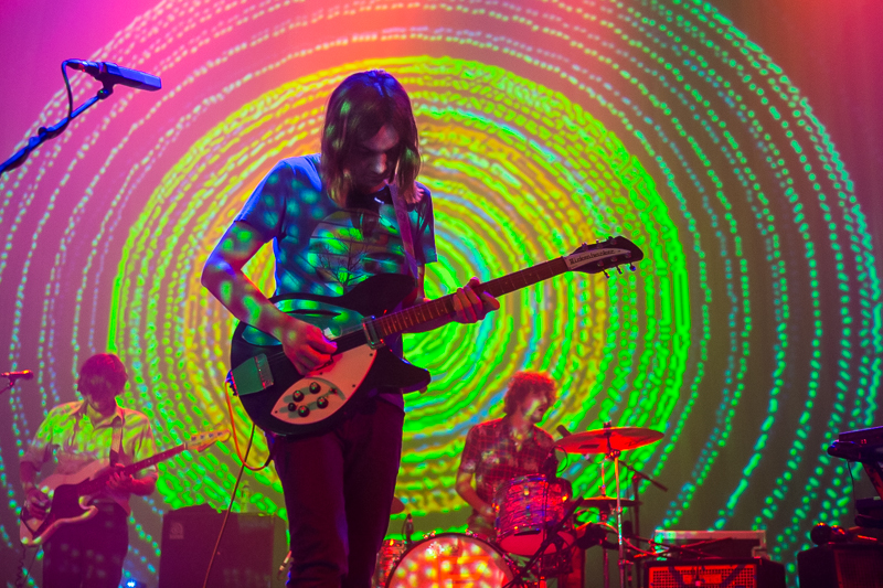 "alt=""Psychedelic musician plays guitar at light show concert"""