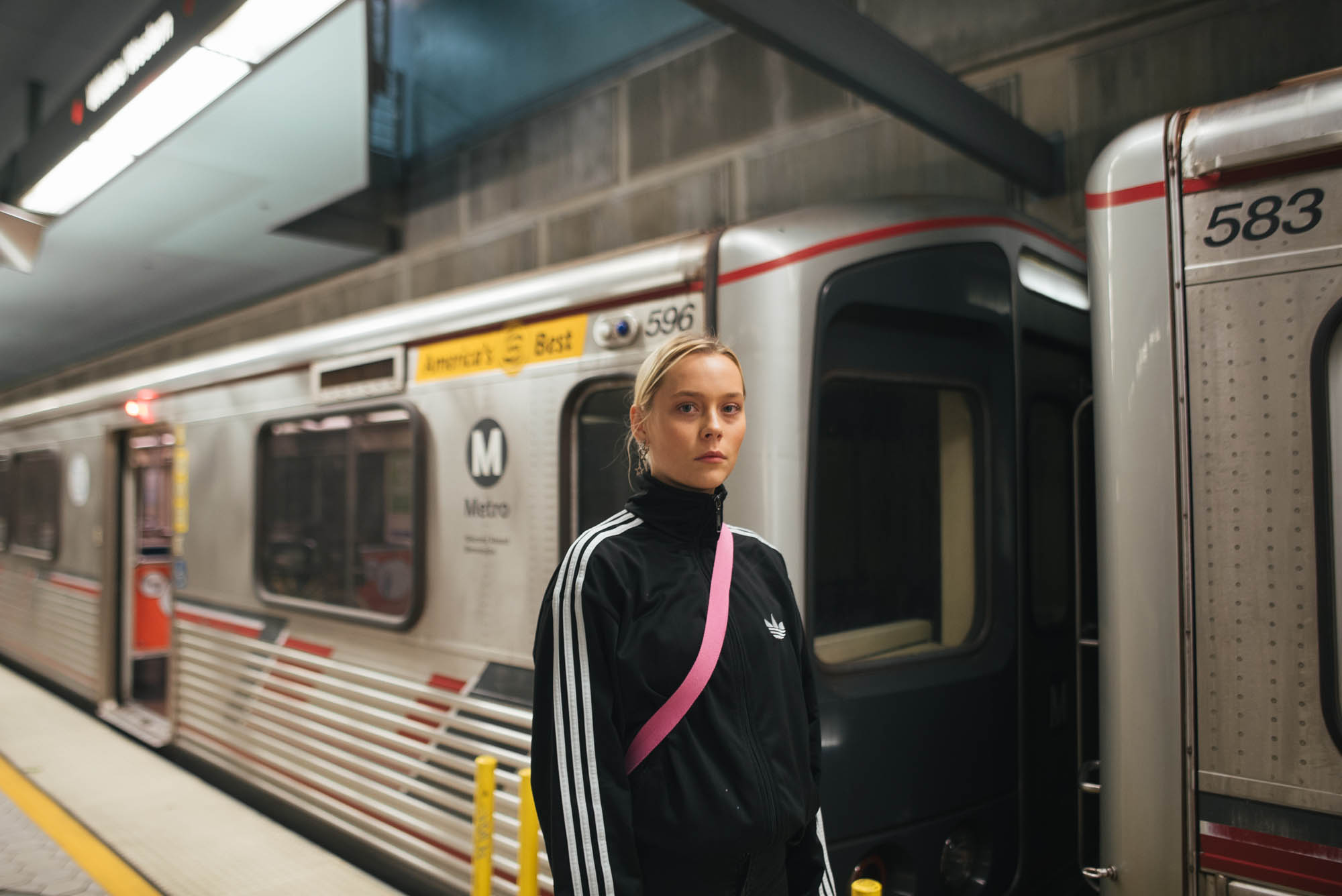 "alt=""Woman in adidas zip up at metro station"""