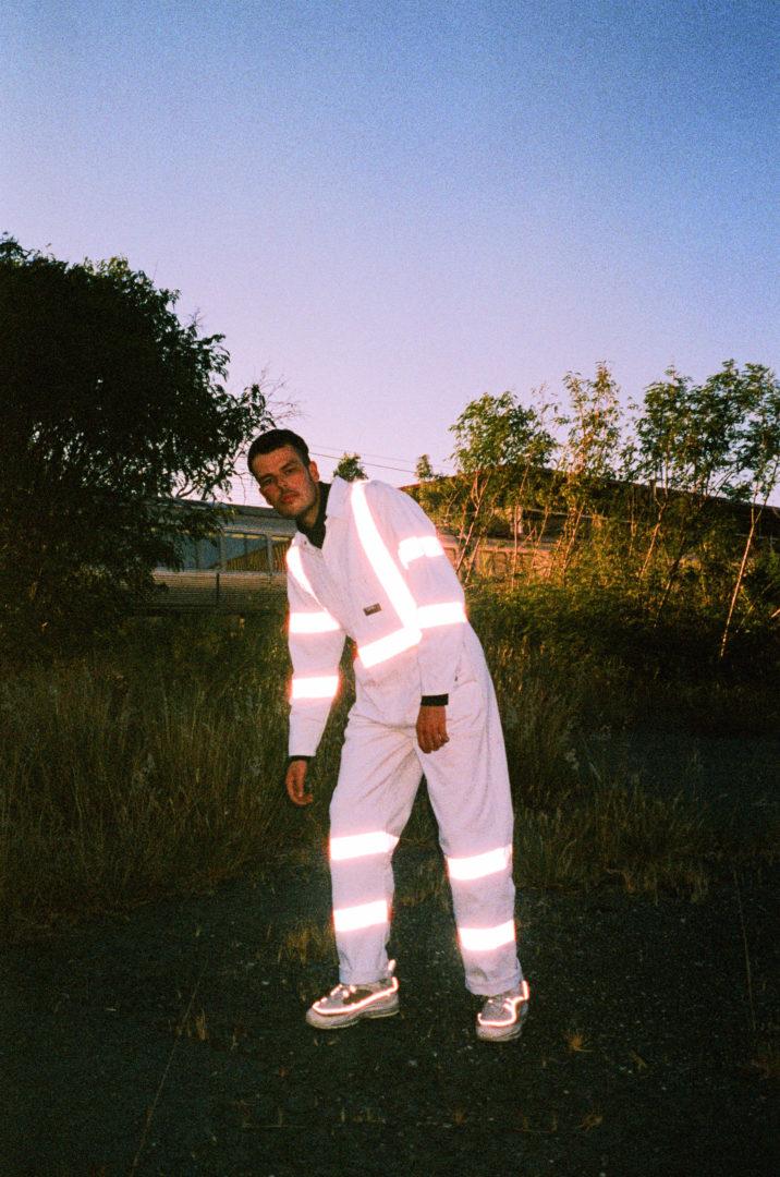 "alt=""Golden vessel musician in white workers suit in grass field"""