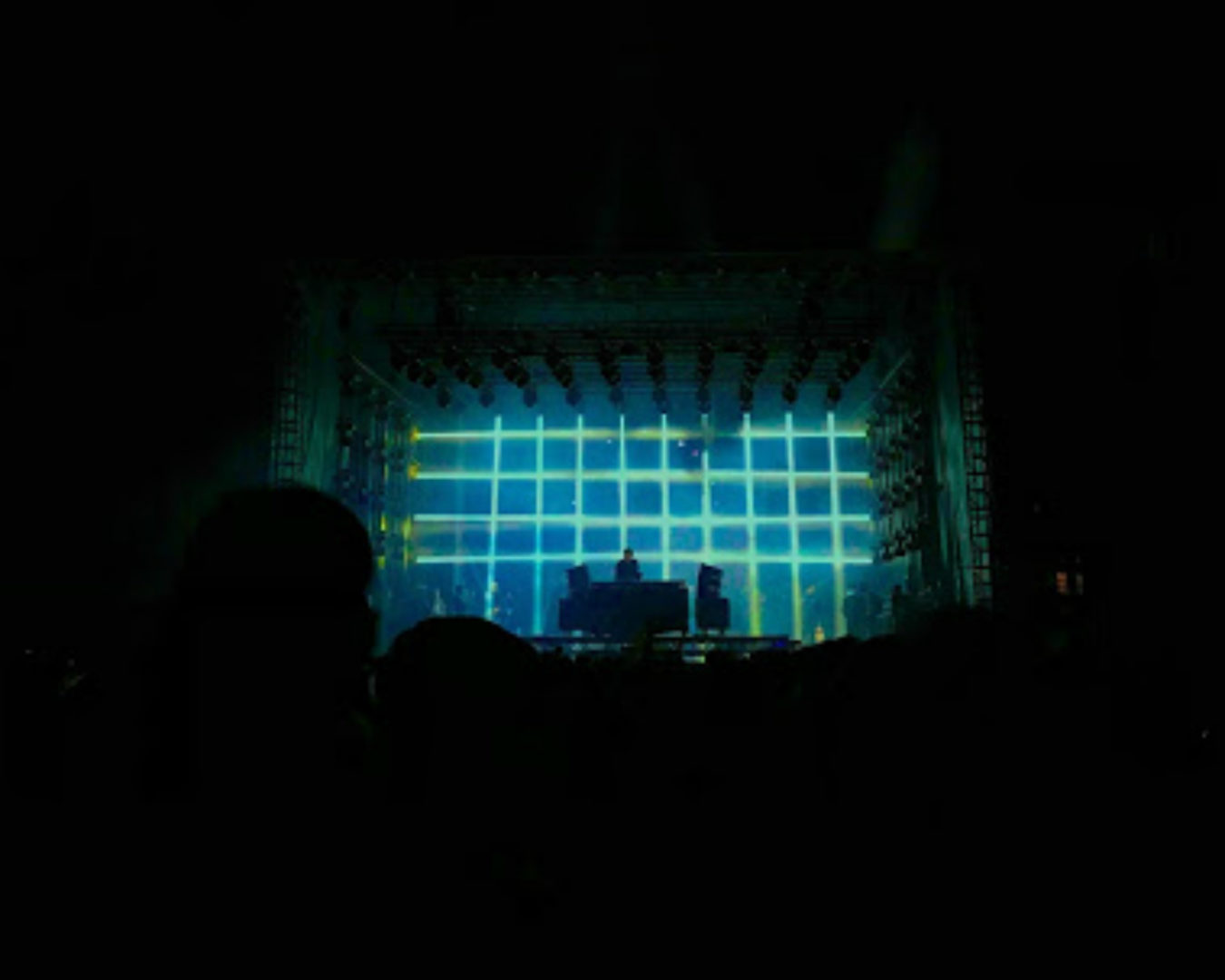 "alt=""lit up stage at electronic musical festival"""