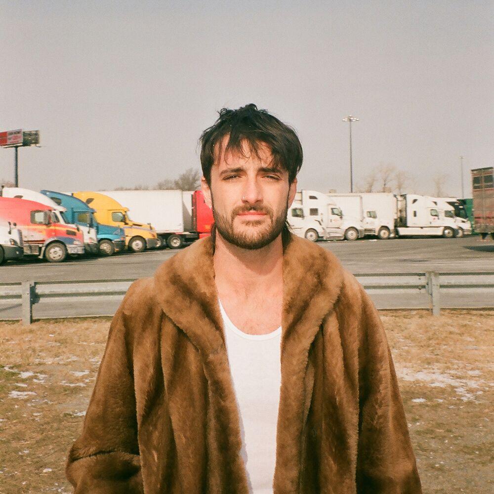 "alt=""Akurei wearing fur coat in front of truck depot"""