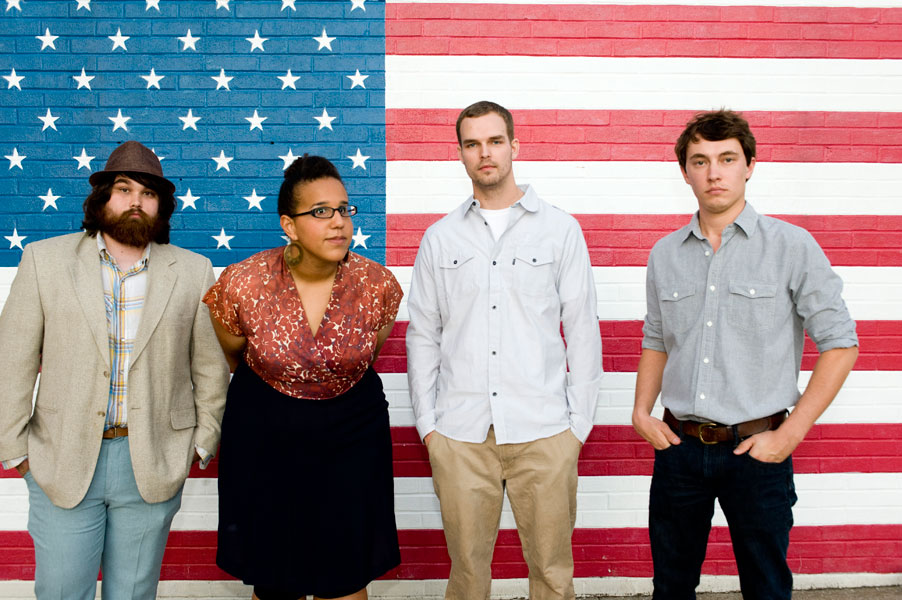 "alt=""Alabama Shakes band in front of American flag"""